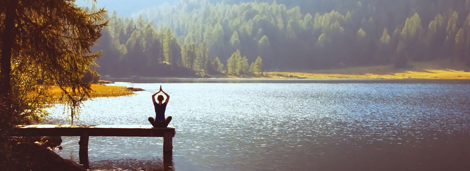 Eine Frau macht Yoga auf einem Steg an einem See