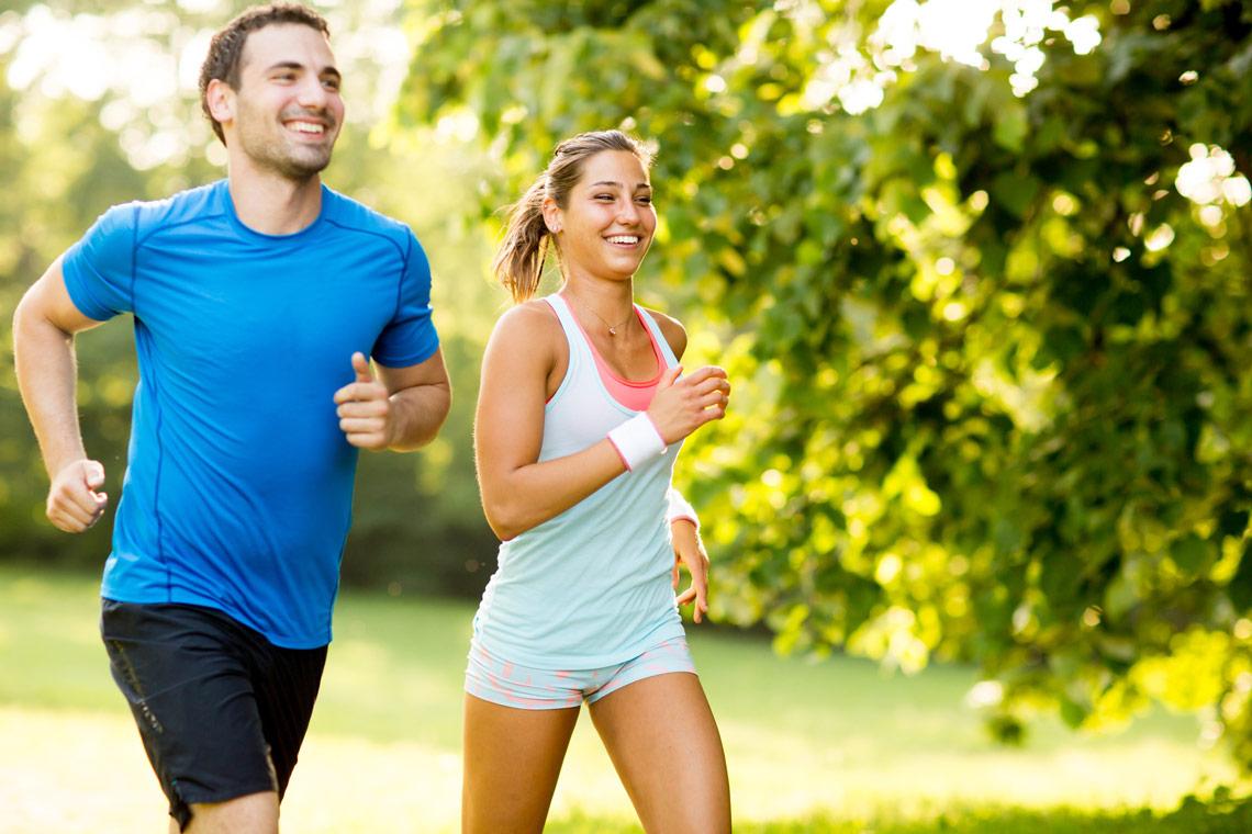 Ein junges Paar joggt in der Natur.