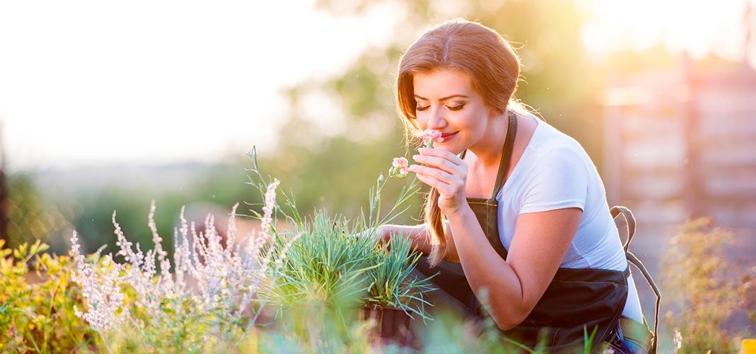 Junge Frau kniet im Garten und riecht an einer Blume