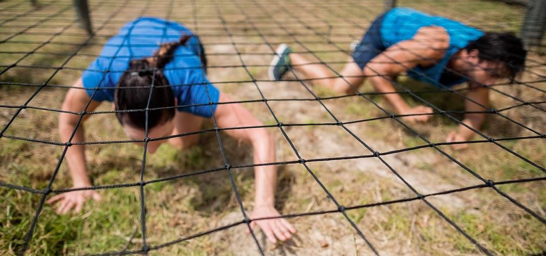 Beim Crawling zeigen dir Coaches wieder, wie du es richtig machst: Arme und Beine werden versetzt nach vorne bewegt, dabei das Bein bis vorne zur Hand gezogen.