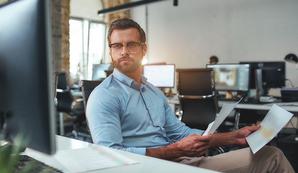 Mann sitzt vor Bildschirm im Büro.